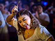 19 OCTOBER 2018 - BANGKOK, THAILAND: Bloods pours off a woman's tongue after she sliced it as a sign of fealty to Devi during Navratri observances in Bangkok. Navratri is a nine night (10 day) long Hindu celebration that marks the end of the monsoon and honors of the divine feminine Devi (Durga). The festival is celebrated differently in different parts of India, but the common theme is the battle and victory of Good over Evil based on a regionally famous epic or legend such as the Ramayana or the Devi Mahatmya. Navratri is celebrated throughout Southeast Asia in communities that have a large Hindu population. Because Navratri honors the feminine Devi, Navratri is especially popular with Thai women and transgendered people.  PHOTO BY JACK KURTZ