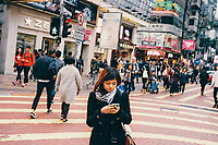 A woman crossing the street in Causeway Bay in Hong Kong.