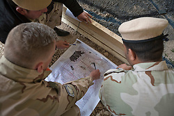 © Licensed to London News Pictures. 30/03/2015. Erbil, Iraq. A Dutch coalition forces instructor helps peshmerga officers with map planning exercise during a coalition forces run training package at a military training area near Erbil, Iraq.<br /> <br /> The training is part of a four week long package, the first to be held with a complete peshmerga battalion, run by coalition forces mobile training teams (MTT) in Kurdistan with the aim to make the peshmerga more efficient in combatting the Islamic State. Photo credit: Matt Cetti-Roberts/LNP