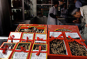 Caterpillar fungus gift boxes for sale in a traditional medical pharmacy, Kunming, China. The parasitic fungus Cordyceps sinensis attacks the larvae of the ghost moth Hepialus armoricanus, and grows into the body of the caterpillar. The fungus literally takes over the caterpillar, forming a hard, brown, mummy-like fungus sculpture of the caterpillar. The fungus is used to treat asthma, colds, jaundice, and tuberculosis and is very expensive: It sells for 4,000 yuan ($500 U.S.) per pound. Image from the book project Man Eating Bugs: The Art and Science of Eating Insects.