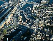 Nederland, Amsterdam, Damrak, 17-10-2005; links centraal Station met Stationsplein, met trams en bussen; midden: water van het Open Havenfront (voor CS) met rondvaartboten, rechts het Damrak met de bouwput van de Noord-Zuidlijn van de Amsterdamse Metro (in deze bouwput wordt het eerste caisson afgezonken); .verder zichtbaar (midden boven) Prins Hendrikkade met St.Nikolaaskerk en Scheepvaarthuis; stadshart, centrum,  openbaar vervoer, toerisme, economie; zie ook andere (lucht)foto's van deze locatie.foto Siebe Swart