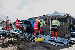 Licensed to London News Pictures. 03/03/2016. Calais, France. Contractors work to dismantle and clear the makeshift shelters in which thousands have lived through the winter. French authorities are clearing the southern half of the Calais 'Jungle' camp, which charities estimate to contain 3,500 people. Photo credit : Rob Pinney/LNP