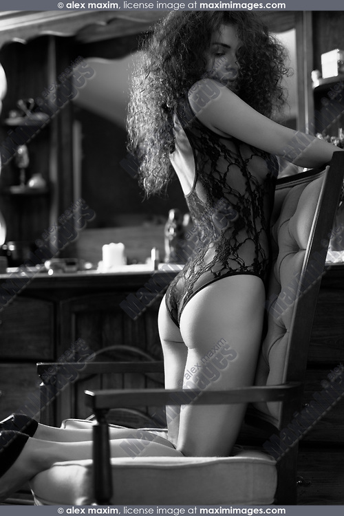Artistic boudoir black and white portrait of a sexy beautiful woman standing on her knees in a chair by a dresser mirror with thoughtful sensual expression wearing lacy underwear. Vintage retro French style.