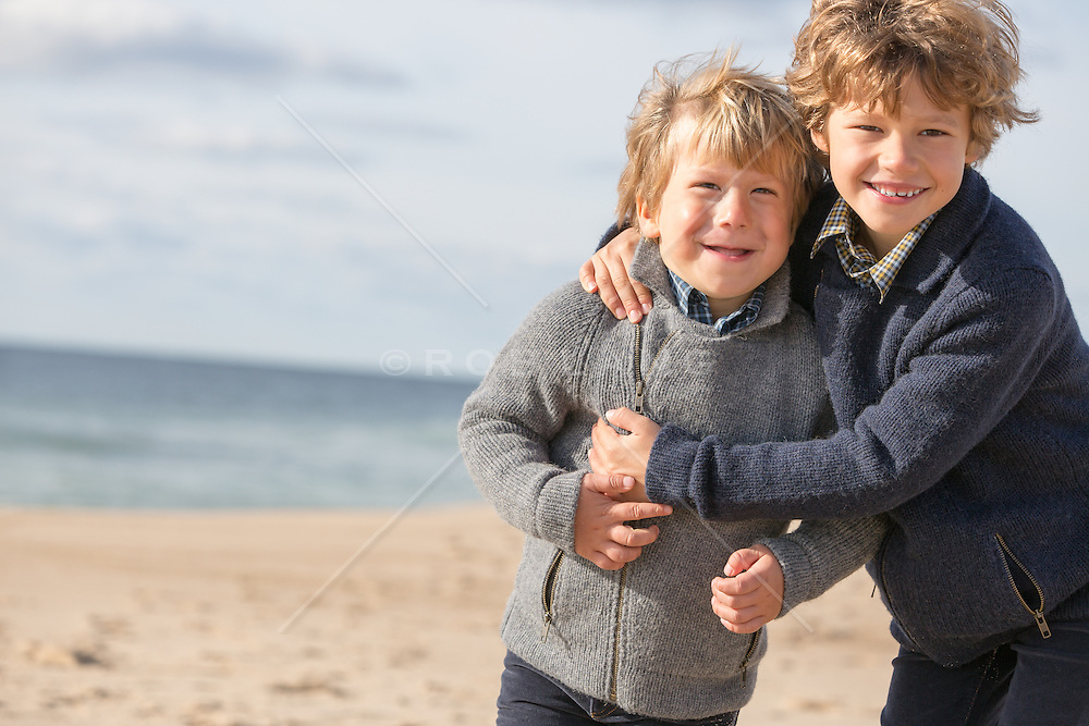two brothers hugging and enjoying time together on the beach in The Hamptons