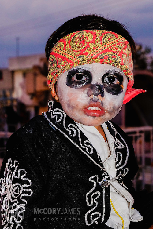 A young boy with dressed up for Dia de los Muertos
