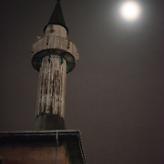 The moon shines through light mist onto a tower in Karakoy, Istanbul.
