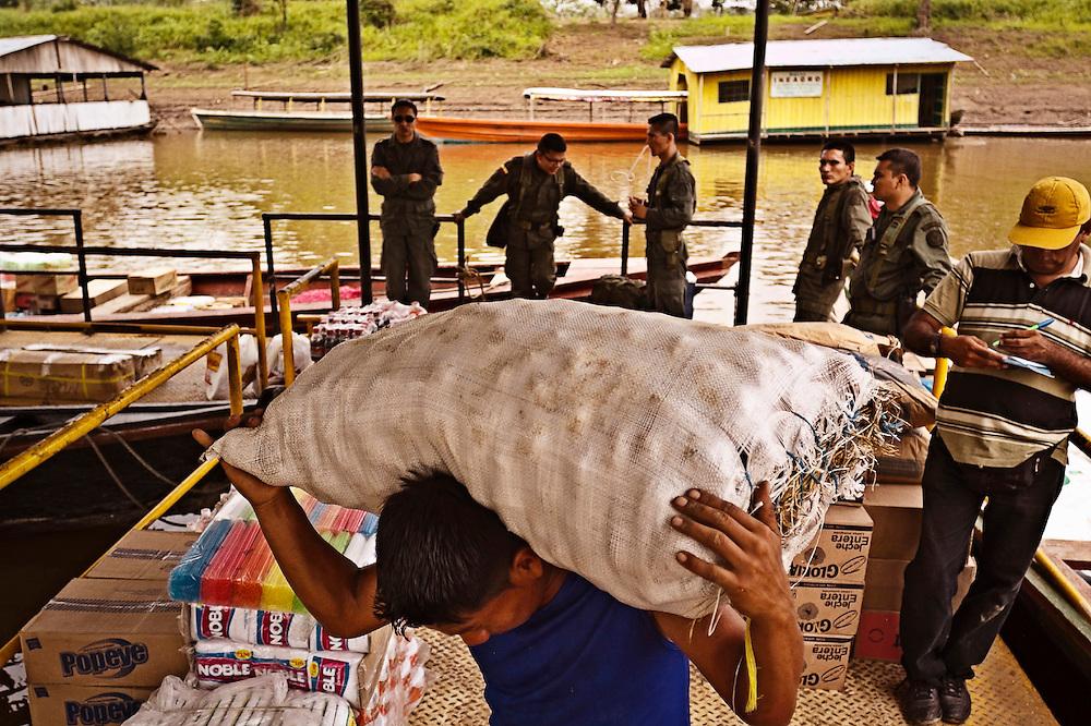 Colombia, Puerto Nari&ntilde;o, 2010. Puerto Nari&ntilde;o. <br /> Un hombre descarga mercanc&iacute;as en el puerto secundario del Amazonas colombiano. El poblado recibe el nombre de Puerto Nari&ntilde;o por una embarcaci&oacute;n de carga, el Vapor Nari&ntilde;o, que encall&oacute; en estas aguas a principios del siglo XX. Actualmente, narcotraficantes y guerrilleros se disputan el poder en este territorio, que forma parte de la ruta de la coca&iacute;na en esta zona de Am&eacute;rica Latina. La presencia de polic&iacute;as y militares se volvi&oacute; constante en los &uacute;ltimos a&ntilde;os.<br /> A man unloads his merchandise at a secondary port on the Colombian Amazon. The town is called Port Nari&ntilde;o by a boat, the Nari&ntilde;o Steam, which ran aground in these waters at the beginning of the 20th century.  Currently, drug traffickers and guerrillas compete for power in this territory, which is part of the route used for cocaine trafficking in this part of Latin America. The presence of police and the military has become constant in the last years.