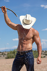 hot muscular cowboy hosing himself off outdoors