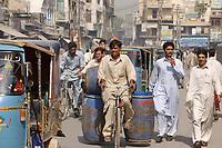 19 OCT 2001, RAWALPINDI/PAKISTAN:<br /> Ein Mann transportiert riesige Faesser auf einem Fahrrad durch den Verkehr von Rawalpindi in der Naehe von Islamabad<br /> IMAGE: 20011019-02-019