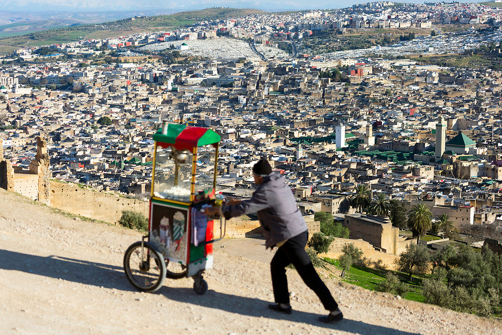 Fez, Morocco - 3rd FEBRUARY 2018 - Popcorn seller pushes a cart up to a popular view point over the old Fez Medina, Middle Atlas Mountains, Morocco.