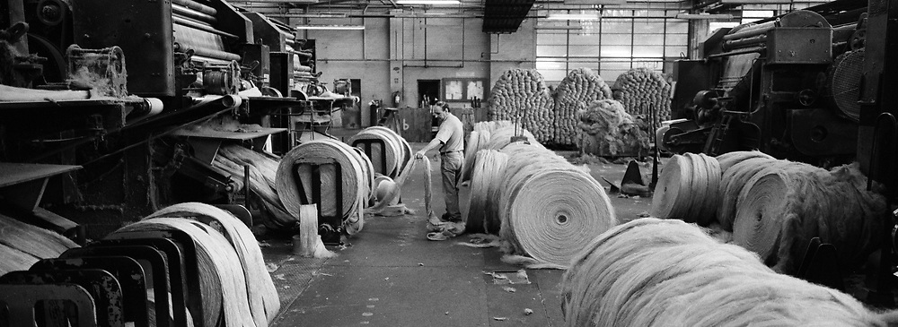 A worker supervising a machine at Tay Spinners mill in Dundee, Scotland. This factory was the last jute spinning mill in Europe when it closed for the final time in 1998. The city of Dundee had been famous throughout history for the three 'Js' - jute, jam and journalism.