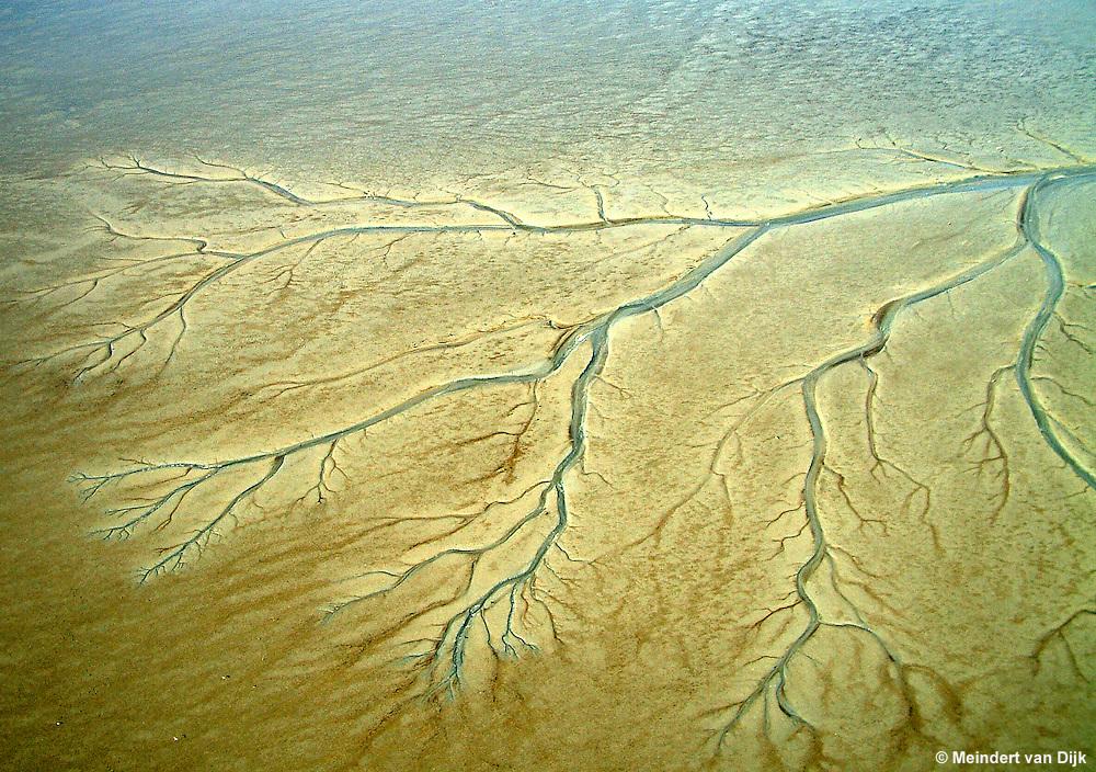 Waddenzee, 14 maart 2003. Tijdens eb drooggevallen zandplaten met geulen en prielen.