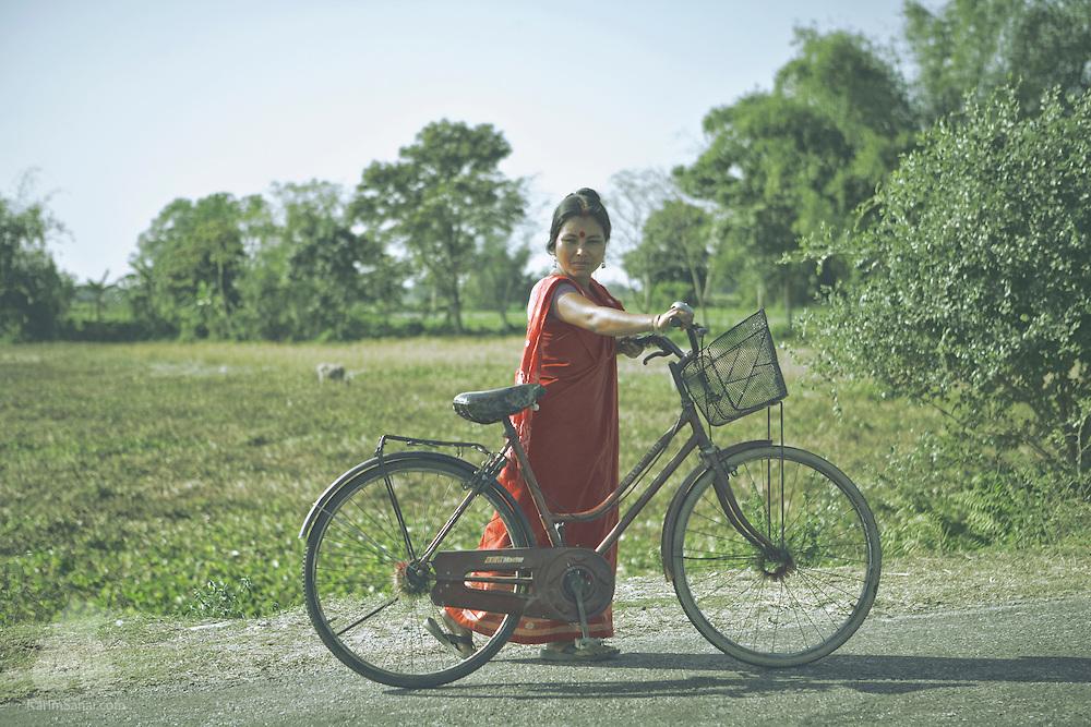 A woman pushing her bicycle, Botabari, Assam, India