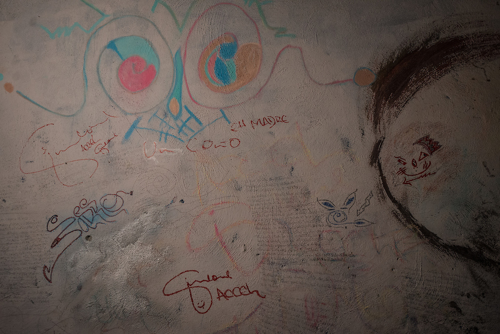 """MARACAY, VENEZUELA - JULY 4, 2016: Original hip hop songs written on the bedroom walls of schizophrenic Accel Simeone. On days when there is enough medicine to clear his mind, Accel writes new hip-hop lyrics. He has written dozens of songs, one was about his relationship with his brother Gerardo, who is also schizophrenic. Another, called """"The Lights Are Out,"""" tells of the constant blackouts his neighborhood faces.  PHOTO: Meridith Kohut for The New York Times"""