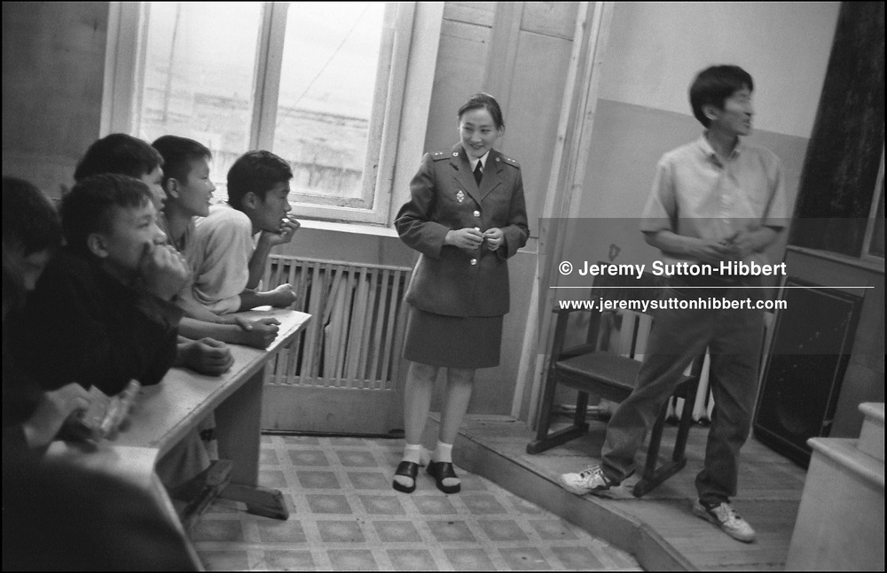 A female prison guard watches over one of the lessons in the school room of the Childrens Prison, Ulaan Baatar, Mongolia.