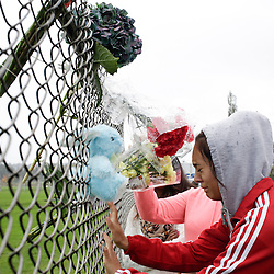Student Tyanna Davis cries after placing flowers on a fence outside Marysville-Pilchuck High School the day after a shooting at the school in Marysville, Washington October 25, 2014. A student shot dead a female classmate and wounded four others when he opened fire in the cafeteria of his Washington state high school on Friday, apparently after a fight with fellow students, officials said. The shooter, a homecoming prince at Marysville-Pilchuck High School, took his own life as his classmates scrambled to safety in the latest outburst of deadly violence at an American school. REUTERS/Jason Redmond (UNITED STATES - Tags: CRIME LAW EDUCATION)