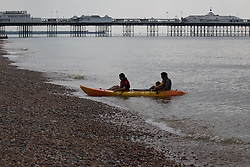 © Licensed to London News Pictures. 31/05/2014. Brighton, UK. A family arrive back from an early morning trip out on the sea in their kajak. The weekend is expected to reach temperatures of 20C down the South Coast according to the MET office. Photo credit : Hugo Michiels/LNP