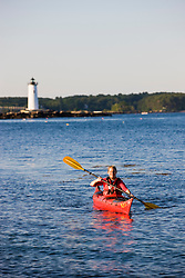 A woman kayaking in New Castle, New Hampshire. Portsmouth Harbor Light is in the distance.