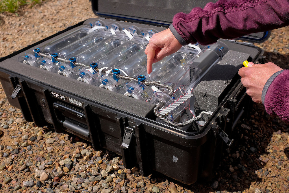 Gabrielle Pétron, a climate scientist from the University of Colorado Boulder, working in NOAA's Earth System Research Laboratory, takes a moment to explain how air quality samples are made in the field using the NOAA mobile Laboratory, showcasing the specialized equipment, such as the glass flasks containing air samples that will be sent back for analysis.