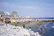 Crowded beach with pyramidal shaped modern hotels, La Grande-Motte, Herault, France 1972