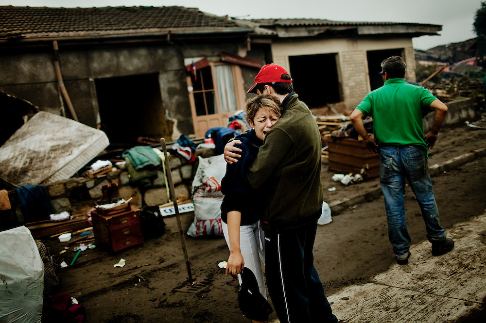 """Dennise Pinochet, 24, cries in front of her destroyed house and completely devastated neighborhood. She was crying out """"we have to leave this doomed town"""" Constitucion. Chile. March 01, 2010."""