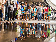 "07 AUGUST 2014 - BANGKOK, THAILAND:  People line up in the street before food distribution started at Pek Leng Keng Mangkorn Khiew Shrine. Thousands of people lined up for food distribution at the Pek Leng Keng Mangkorn Khiew Shrine in the Khlong Toei section of Bangkok Thursday. Khlong Toei is one of the poorest sections of Bangkok. The seventh month of the Chinese Lunar calendar is called ""Ghost Month"" during which ghosts and spirits, including those of the deceased ancestors, come out from the lower realm. It is common for Chinese people to make merit during the month by burning ""hell money"" and presenting food to the ghosts. At Chinese temples in Thailand, it is also customary to give food to the poorer people in the community.       PHOTO BY JACK KURTZ"