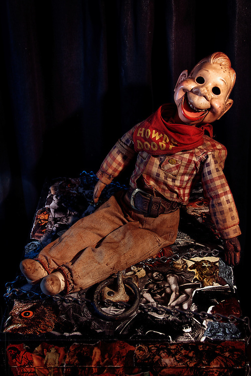 A clash of juxtaposed subject matter featuring a decrepit old Howdy Doody ventriloquist dummy perched on a grimly decorated wooden box featuring a collage of vintage occult images.