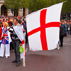 LONDON, UK  29/04/2011. The Royal Wedding of HRH Prince William to Kate Middleton. A spectator with a large St Georges Cross flag watches the big screen in Trafalgar Square. Photo credit should read CLIFF HIDE/LNP. Please see special instructions. © under license to London News Pictures