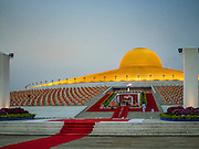 "22 FEBRUARY 2016 - KHLONG LUANG, PATHUM THANI, THAILAND: Monks sit around the chedi and listen to the abbot (in the center of the frame) during the Makha Bucha Day service at Wat Phra Dhammakaya.  Makha Bucha Day is a public holiday in Cambodia, Laos, Myanmar and Thailand. Many people go to the temple to perform merit-making activities on Makha Bucha Day, which marks four important events in Buddhism: 1,250 disciples came to see the Buddha without being summoned, all of them were Arhantas, Enlightened Ones, and all were ordained by the Buddha himself. The Buddha gave those Arhantas the principles of Buddhism, called ""The ovadhapatimokha"". Those principles are:  1) To cease from all evil, 2) To do what is good, 3) To cleanse one's mind. The Buddha delivered an important sermon on that day which laid down the principles of the Buddhist teachings. In Thailand, this teaching has been dubbed the ""Heart of Buddhism."" Wat Phra Dhammakaya is the center of the Dhammakaya Movement, a Buddhist sect founded in the 1970s and led by Phra Dhammachayo. The temple is famous for the design of its chedi, which some have likened to a flying saucer or UFO.      PHOTO BY JACK KURTZ"