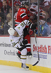 Oct 8; Newark, NJ, USA; Dallas Stars right wing Adam Burish (16) hits New Jersey Devils defenseman Anton Volchenkov (28) into the boards during the second period at the Prudential Center.