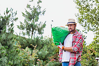 Portrait of male gardener carrying sack of soil on his shoulder while walking in garden shop