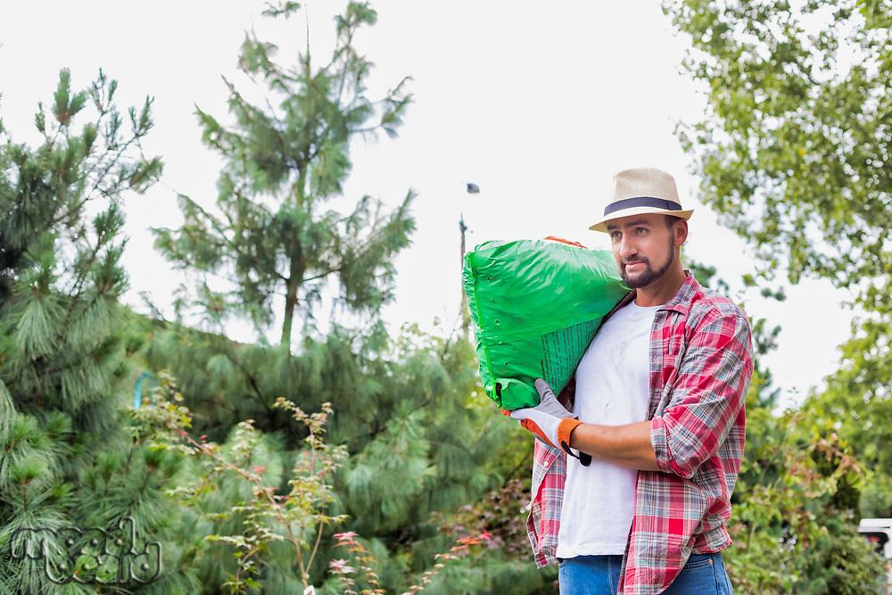 Portrait of male gardener carrying sack of soil on his shoulder while walking in garden shop