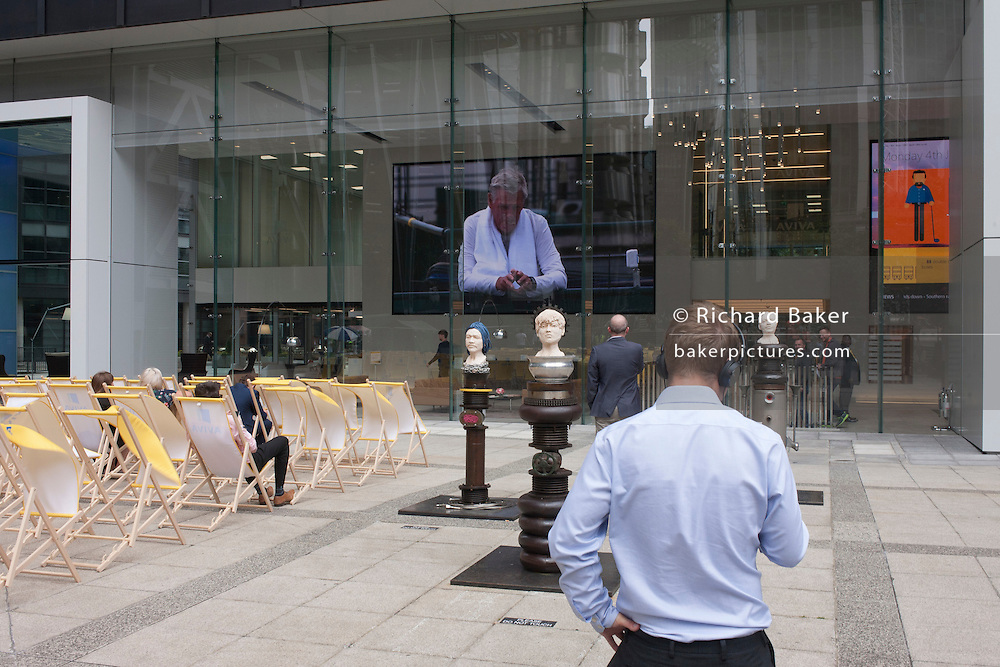 City workers watch a womens' tennis match on a huge screen outside the City of London headquarters of insurance company Aviva during Wimbledon fortnight, on 4th July, London, United Kingdom. Sculpture entitled 'Of Saints and Sailors' by the artist Benedetto Pietromarchi is being shown here during the annual open-air arts exhibition, 'Sculpture in the City' when 17 contemporary installations by artists in 20 locations in the Square Mile, London's financial heart founded by the Romans in the 1st Century.