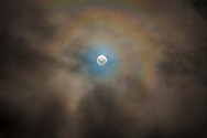 The nearly Full Moon of April 10, 2017 as seen from Australia, and embedded in fast-moving low cloud adding the colourful corona effect around the Moon from water-droplet diffraction. <br /> <br /> Being in the southern hemisphere, the Full Moon appears &ldquo;upside-down&rdquo; compared to a northern view.<br /> <br /> This is a 6-image blend of exposures from 1/2 second to 1/20-second to capture both the faint clouds and bright Moon. I blended them with luminosity masks (generated with ADP Panel+ Pro) rather than attempting an HDR stack which rarely works well for the Moon.