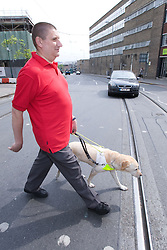 Vision impaired man and guide dog crossing the road at a Pelican crossing,
