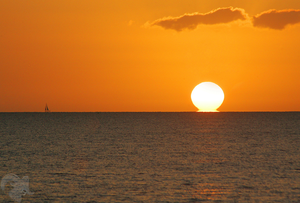 A lone sailboat sails into the sunset off Maui, Hawaii.