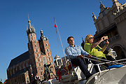 A tourist riding alongside a carriage driver uses her phone to photograph sites beneath the towers of the Church of St Mary on Rynek Glowny market square, on 22nd September 2019, in Krakow, Malopolska, Poland.