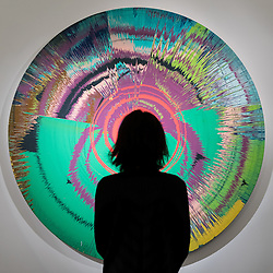 """© Licensed to London News Pictures. 01/11/2016. London, UK. A staff member views """"Beautiful, hallo, space-boy"""" by Damian Hirst, a collaboration with David Bowie, est. GBP250-350k. The first look of """"Bowie / Collector"""", artworks from the late David Bowie's personal art collection, ahead of their sale later this month at Sotheby's. Photo credit : Stephen Chung/LNP"""