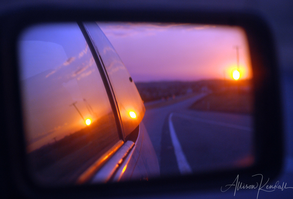 A vivid sunset is captured in the rearview mirror of a speeding car