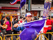 "19 FEBRUARY 2015 - BANGKOK, THAILAND: A man sells Thai flags and the purple flag which is the personal flag of Princess Maha Chakri Sirindhorn, who opened Chinese New Year festivities in Bangkok. 2015 is the Year of Sheep in the Chinese zodiac. The Sheep is the eighth sign in Chinese astrology and ""8"" is considered to be a lucky number. It symbolizes wisdom, fortune and prosperity. Ethnic Chinese make up nearly 15% of the Thai population. Chinese New Year (also called Tet or Lunar New Year) is widely celebrated in Thailand, especially in urban areas that have large Chinese populations.    PHOTO BY JACK KURTZ"