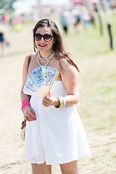 © Licensed to London News Pictures. 13/06/2014. Isle of Wight, UK.   A girls in a white summery dresses cooling herself with a fan in the hot sunny morning weather at Isle of Wight Festival 2014.   The Isle of Wight festival is an annual music festival that takes place on the Isle of Wight. Photo credit : Richard Isaac/LNP