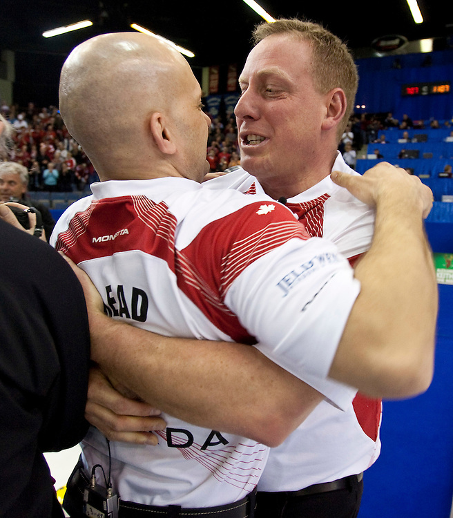 Canadian third Jon Mead, left, and lead Steve Gould celebrate their victory over Scotland in the gold medal game at the Ford World Men's Curling Championships in Regina, Saskatchewan, April 10, 2011.<br /> AFP PHOTO/Geoff Robins