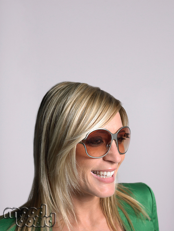 Woman with blonde hair and sunglasses in studio