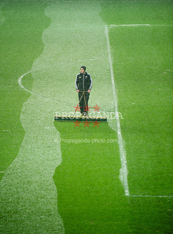 SWANSEA, WALES - Wednesday, January 23, 2013: A groundsman clears snow from the pitch at Swansea City's Liberty Stadium as snow falls before the Football League Cup Semi-Final 2nd Leg match against Chelsea. (Pic by David Rawcliffe/Propaganda)