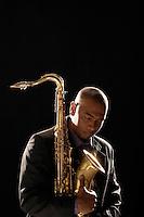 Pensive man holding saxophone eyes closed