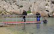 Divers shoreline clear blue sea water, Mgarr ix-Xini coastal inlet, island of Gozo, Malta
