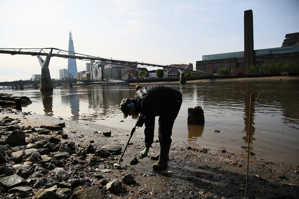 A mudlarker looks for items on the bank of the river Thames near Millennium Bridge in London, Britain May 22, 2016. When the river Thames is at low tide, mudlarkers scour the shore for historical artefacts and remains from there City of London's ancient past. Finds can date back to Roman times to when the city was found up until more recent times. Anyone can walk along the river and look for finds, but the uses of metal detectors and digging is restricted. Mudlarkers need to be licences by the Port of London Authority. All find should be register with the Museum of London. REUTERS/Neil Hall