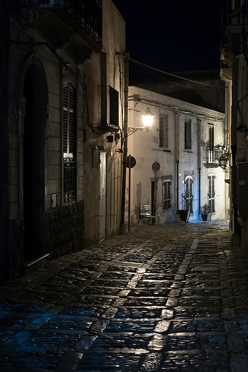 Lamps shining on stone cobbles at night in cobbled street alleyway in Erice, Sicily, Italy
