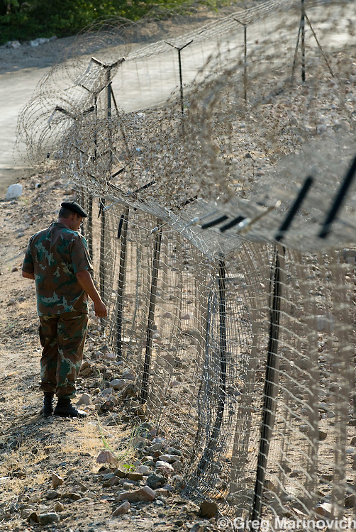 Beit Bridge, Limpopo, An SANDF soldier checks the fence at the South Africa - Zimbabwe border at Limpopo River, crossable by foot in the dry season. Many Zimbabweans aredesperate to get into South Africa. 2007. Photo Greg Marinovich / Storytaxi.com