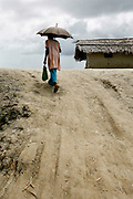 A man with an umbrella walks up the steep edge of a flood levee built to shield the Burigoalini against flooding and storm surge. Bangladesh is prone to a double whammy of flooding and drought caused by the melting glaciers of Himalaya.